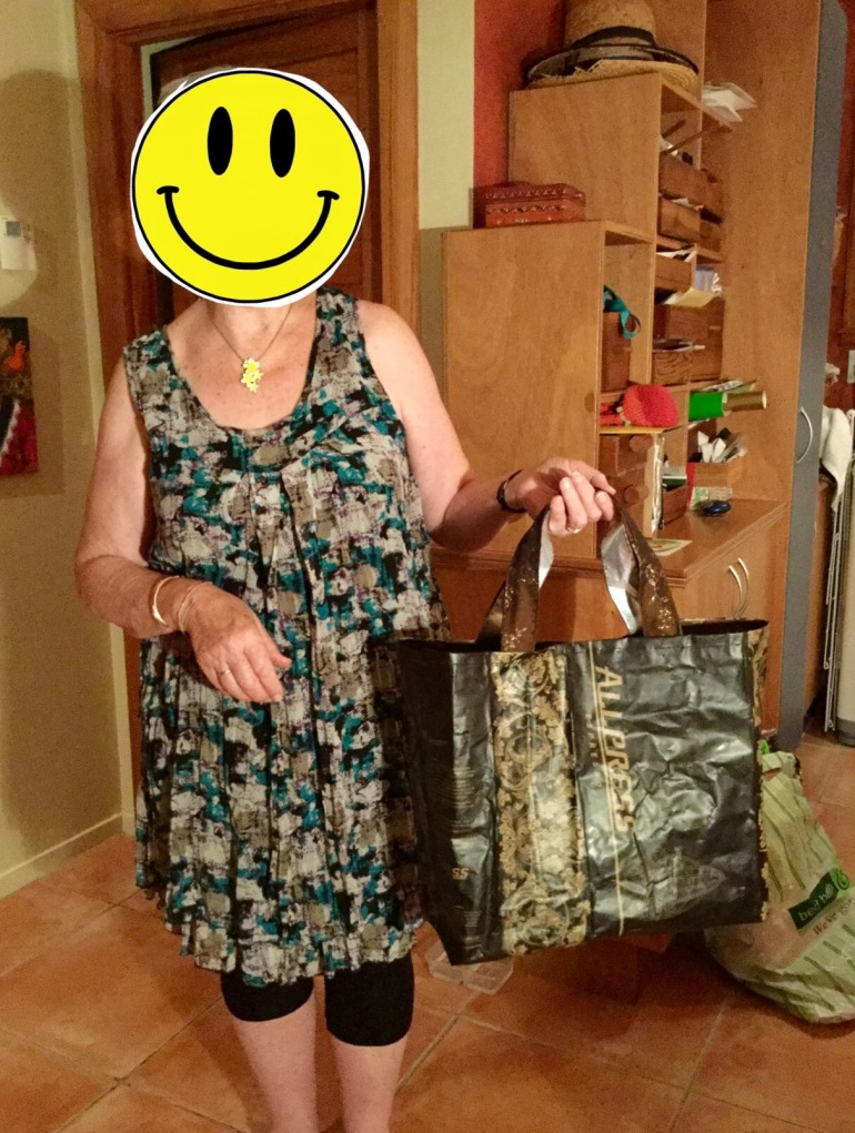 A happy student having made herself a handbag out of coffee sacks during a sewing tutorial.